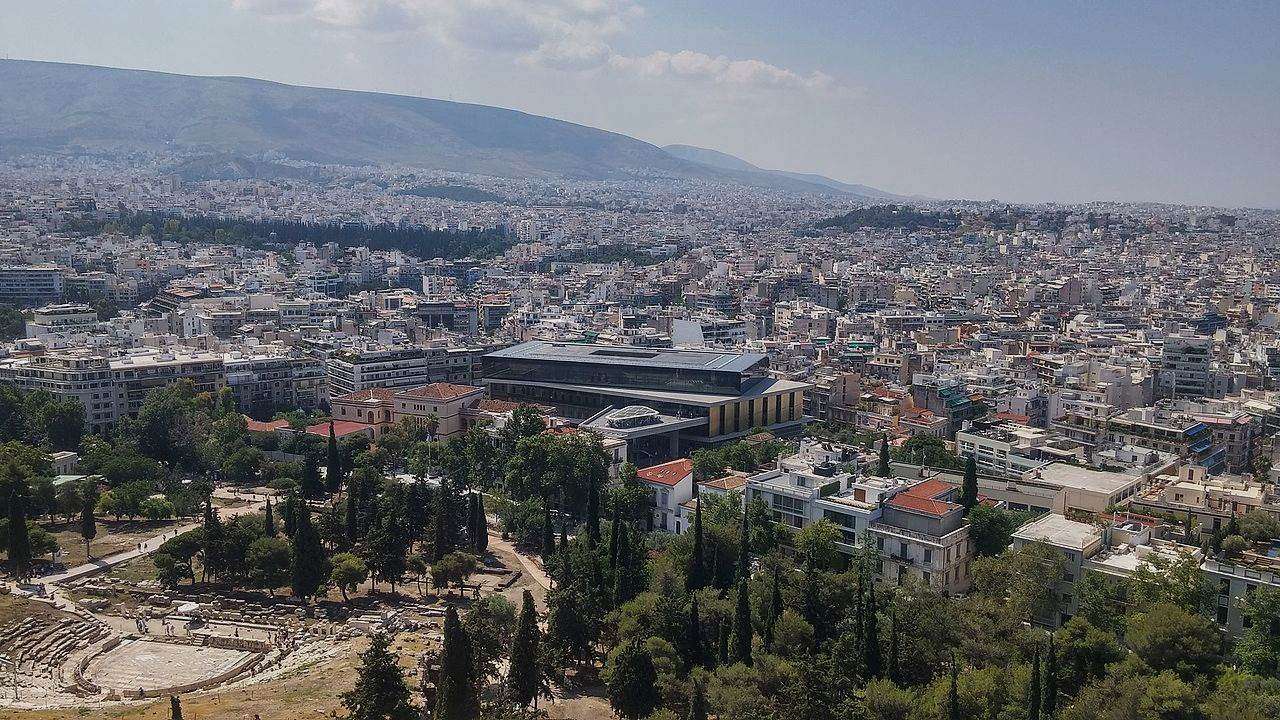 View from the Acropolis in Athens with Theatre of Dionysus Eleuthereus, Acropolis Museum, and city towards the horizon, 2017